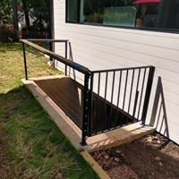 Home contractors remodeling railing on outside deck