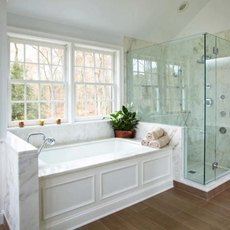Large glass shower and marble tub bathroom design.
